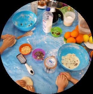 Niños amasando e ingredientes de cocina sobre una mesa